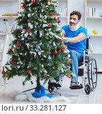 Купить «Injured disabled man celebrating christmas at home», фото № 33281127, снято 26 июля 2017 г. (c) Elnur / Фотобанк Лори