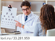 Купить «Doctor optician with letter chart conducting an eye test check», фото № 33281959, снято 30 марта 2017 г. (c) Elnur / Фотобанк Лори