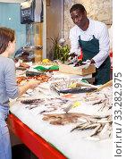 Jolly salesman proposing young woman raw clams. Стоковое фото, фотограф Яков Филимонов / Фотобанк Лори