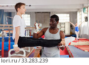 Купить «Male coach training teenage boy on gymnastic equipment at acrobatic hall», фото № 33283239, снято 17 января 2019 г. (c) Яков Филимонов / Фотобанк Лори