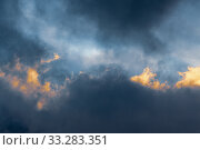 Fluffy clouds illuminated by disappearing rays at sunset, thunderclouds floating across sky to change season weather. Stunning meteorology background. Стоковое фото, фотограф А. А. Пирагис / Фотобанк Лори