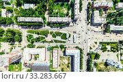 Купить «Aerial city view with crossroads and roads, houses, buildings, parks and parking lots. Sunny summer panoramic image», фото № 33283667, снято 29 марта 2020 г. (c) Александр Маркин / Фотобанк Лори