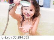 Купить «The girl pours to herself on a hand water from a shower, sitting in the bathroom. Focus on drops», фото № 33284355, снято 6 февраля 2019 г. (c) Екатерина Кузнецова / Фотобанк Лори