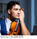 Купить «Young musician man practicing playing violin at home», фото № 33285875, снято 15 августа 2017 г. (c) Elnur / Фотобанк Лори