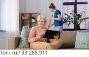 Купить «old woman with tablet pc and housekeeper at home», видеоролик № 33285911, снято 19 января 2020 г. (c) Syda Productions / Фотобанк Лори