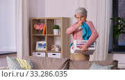senior woman picking clothes for laundry at home. Стоковое видео, видеограф Syda Productions / Фотобанк Лори