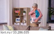 Купить «senior woman picking clothes for laundry at home», видеоролик № 33286035, снято 19 января 2020 г. (c) Syda Productions / Фотобанк Лори