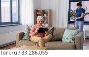 Купить «old woman with tablet pc and housekeeper at home», видеоролик № 33286055, снято 19 января 2020 г. (c) Syda Productions / Фотобанк Лори