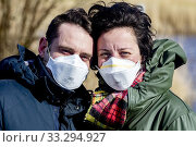 KINDERDIJK - A woman wearing a surgical facemask due the coronavirus (COVID-19). All face masks are sold out in The Netherlands. On the background the famous windmills of Kinderdijk. Редакционное фото, фотограф Niels Ralph Wenstedt / age Fotostock / Фотобанк Лори