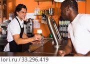 Купить «Young man barman giving beer with foam to man client», фото № 33296419, снято 28 августа 2019 г. (c) Яков Филимонов / Фотобанк Лори
