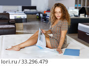 Купить «Young attractive woman choosing right mattress with booklet in home furnishings store», фото № 33296479, снято 22 октября 2018 г. (c) Яков Филимонов / Фотобанк Лори