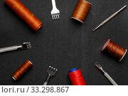 Leather crafting DIY tools and threads lies on natural black leather. Стоковое фото, фотограф Бражников Андрей / Фотобанк Лори