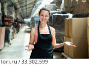 Female in apron standing near shelves with cardboard boxes for packaging. Стоковое фото, фотограф Яков Филимонов / Фотобанк Лори