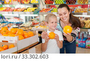 Купить «Portrait of happy woman and her little son choosing oranges at shop», фото № 33302603, снято 20 апреля 2019 г. (c) Яков Филимонов / Фотобанк Лори