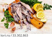 Купить «Raw squid with lemon, garlic and parsley on a wooden cutting board», фото № 33302863, снято 9 апреля 2020 г. (c) Яков Филимонов / Фотобанк Лори