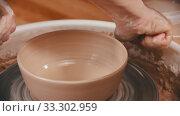 Купить «Pottery - the man is wiping the bottom of the bowl with a yellow sponge», видеоролик № 33302959, снято 5 апреля 2020 г. (c) Константин Шишкин / Фотобанк Лори