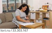 Купить «woman with money, papers and calculator at home», видеоролик № 33303167, снято 24 февраля 2020 г. (c) Syda Productions / Фотобанк Лори