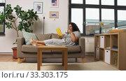Купить «happy young woman reading book on sofa at home», видеоролик № 33303175, снято 24 февраля 2020 г. (c) Syda Productions / Фотобанк Лори
