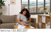 Купить «woman with money, papers and calculator at home», видеоролик № 33303207, снято 24 февраля 2020 г. (c) Syda Productions / Фотобанк Лори