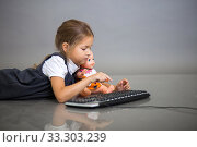 The girl the schoolgirl on a gray background plays with the keyboard from the computer and a doll. Стоковое фото, фотограф Екатерина Кузнецова / Фотобанк Лори