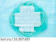 Lot medical surgical face masks on green and blue background. World pandemic insurance, airborne diseases, SARS and influenza. Стоковое фото, фотограф А. А. Пирагис / Фотобанк Лори