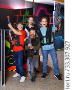 Group portrait of happy teenagers with laser guns having fun on dark lasertag arena. Стоковое фото, фотограф Яков Филимонов / Фотобанк Лори