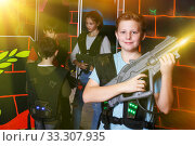 teen boy standing with laser pistol in dark lasertag room. Стоковое фото, фотограф Яков Филимонов / Фотобанк Лори