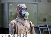 Купить «Mannequin dressed in brown rubber chemical protection suit and black gas mask», фото № 33308243, снято 28 июня 2019 г. (c) Олег Белов / Фотобанк Лори