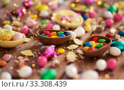 chocolate eggs and candy drops on wooden table. Стоковое фото, фотограф Syda Productions / Фотобанк Лори