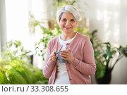 Купить «happy senior woman with cup of tea at home», фото № 33308655, снято 11 января 2020 г. (c) Syda Productions / Фотобанк Лори