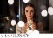 woman with christmas garland lights in glass mug. Стоковое фото, фотограф Syda Productions / Фотобанк Лори