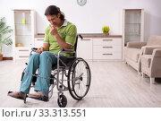 Купить «Young male invalid in wheel-chair suffering at home», фото № 33313551, снято 23 июля 2019 г. (c) Elnur / Фотобанк Лори