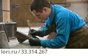 Купить «Concrete industry in workshop - man worker cleaning the form for concrete casting out from the leftovers», видеоролик № 33314267, снято 5 июня 2020 г. (c) Константин Шишкин / Фотобанк Лори