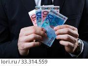 Купить «Young man in formalwear holding money.», фото № 33314559, снято 31 марта 2020 г. (c) PantherMedia / Фотобанк Лори