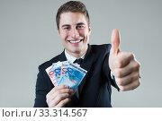 Купить «Young man in formalwear holding money.», фото № 33314567, снято 31 марта 2020 г. (c) PantherMedia / Фотобанк Лори