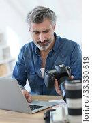 Купить «Photo reporter working in office», фото № 33330619, снято 7 июля 2020 г. (c) PantherMedia / Фотобанк Лори