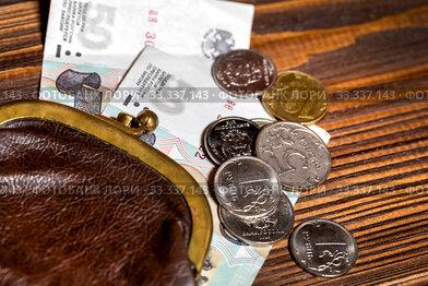 Старый кошелек с монетами и пятидесяти рублевыми купюрами лежит на деревянном столе