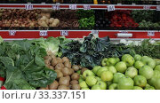 Купить «Large assortment of fresh colorful fruits and vegetables in wicker trays on shelves in supermarket», видеоролик № 33337151, снято 20 ноября 2019 г. (c) Яков Филимонов / Фотобанк Лори