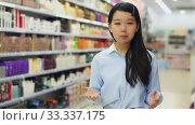 Portrait of cheerful young Asian woman behind counter demonstrating hair dye products. Стоковое видео, видеограф Яков Филимонов / Фотобанк Лори