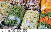 Купить «Fresh cut vegetables in sets prepared for cooking on store showcase», видеоролик № 33337355, снято 16 июля 2020 г. (c) Яков Филимонов / Фотобанк Лори