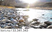 Купить «Dolly slider shot of the splashing water in a mountain river near forest. Wet rocks and sun rays. Horizontal steady movement.», видеоролик № 33341343, снято 3 октября 2018 г. (c) Александр Маркин / Фотобанк Лори