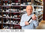 Купить «Attentive pensioner chooses red wine in a liquor store», фото № 33341403, снято 5 апреля 2020 г. (c) Яков Филимонов / Фотобанк Лори