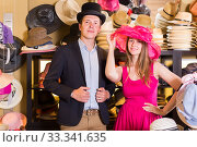 Купить «cheerful female and man choosing hats in the store», фото № 33341635, снято 2 мая 2017 г. (c) Яков Филимонов / Фотобанк Лори