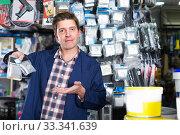 Male seller in hardware store is trading sockets. Стоковое фото, фотограф Яков Филимонов / Фотобанк Лори