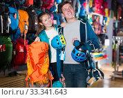 pair chooses backpacks and a helmet for a hike. Стоковое фото, фотограф Яков Филимонов / Фотобанк Лори