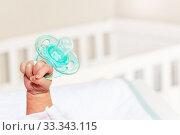 Купить «Tiny infant boy hand fist lift up holding pacifier», фото № 33343115, снято 28 апреля 2019 г. (c) Сергей Новиков / Фотобанк Лори