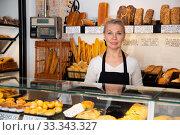 Купить «Saleswoman working at counter of bakery», фото № 33343327, снято 27 мая 2020 г. (c) Яков Филимонов / Фотобанк Лори