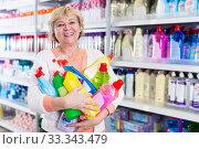 Купить «Happy woman holding chemical goods for cleaning», фото № 33343479, снято 20 декабря 2017 г. (c) Яков Филимонов / Фотобанк Лори