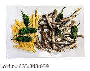 Купить «Delicious dish of fried anchovy with french fries and green pepper», фото № 33343639, снято 4 апреля 2020 г. (c) Яков Филимонов / Фотобанк Лори
