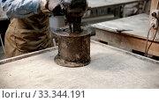 Купить «Concrete industry - man worker putting concrete in the form», видеоролик № 33344191, снято 5 июня 2020 г. (c) Константин Шишкин / Фотобанк Лори
